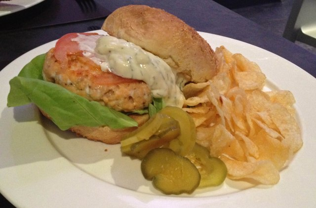 Salmon burger with lettuce, tomato, pickles, and chips, served with lemon-herb mayo at a.cafe in midtown NYC (just off 5th Ave)