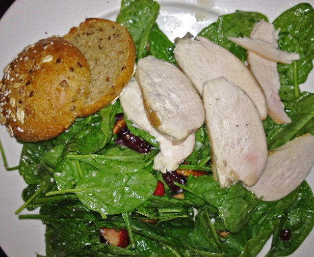Market Salad with spinach, feta cheese, dried cranberries, apples, pistachios, and roast chicken with whole-wheat roll at a.Cafe in NYC