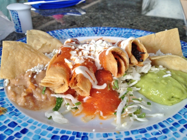 Chicken tacos in red sauce served in hard shell tacos, on a bed of cilantro and shredded cabbage, with re-fried beans, guacamole with crema fresca