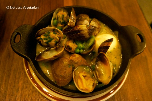 Clams cooked in salsa verde with parsley, asparagus and English peas at Barraca NYC