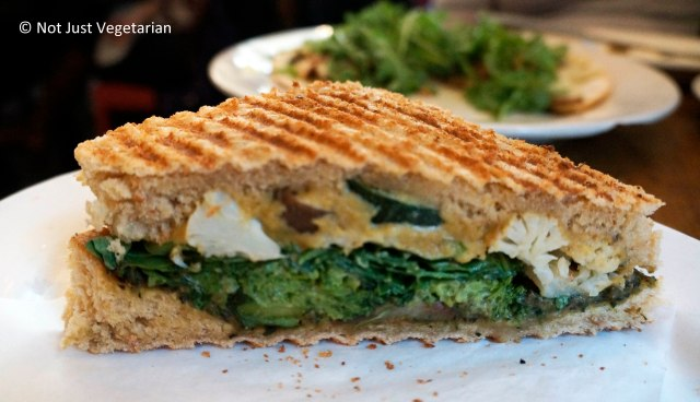 Vegan mediterranean oven-dried seasonal vegetable (Broccoli, cauliflower) Panini with cashew cheese and basil spinach pesto at Peacefood Cafe NYC