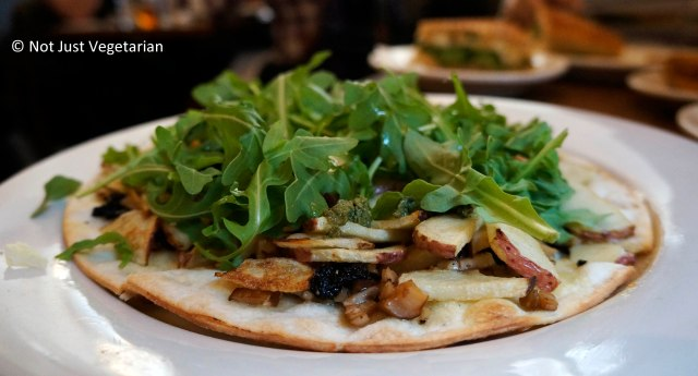 Vegan roasted potato pizza with sauteed mushrooms, arugula, oil cured black olives, and pesto at Peacefood Cafe NYC