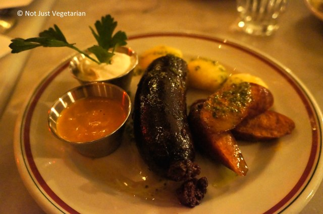 Blood sausage served with chorizo, arepitas, chipotle mayo, and crema fresca at Oficina Latina NYC
