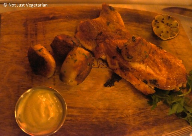 Roasted, deboned half chicken served with grilled lime, cilantro potatoes and a garlic serrano sauce at Oficina Latina NYC