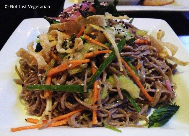Buckwheat soba noodle salad with seasonal vegetables,crispy basil leaves, enoki mushrooms, and wonton crisps in a wasabi-soy vinaigrette at Brickyard Gastropub NYC
