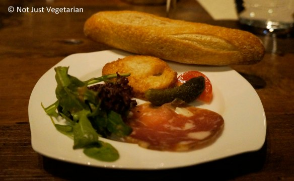 Portion of the charcuterie plate with the mini baguette at Jeanne & Gaston NYC