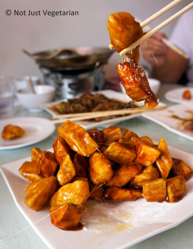 Dessert of sweet potato wedges, apples, and taro coated in corn flour, fried and tossed in hot sticky syrup at Lao Dong Bei in Flushing, NY