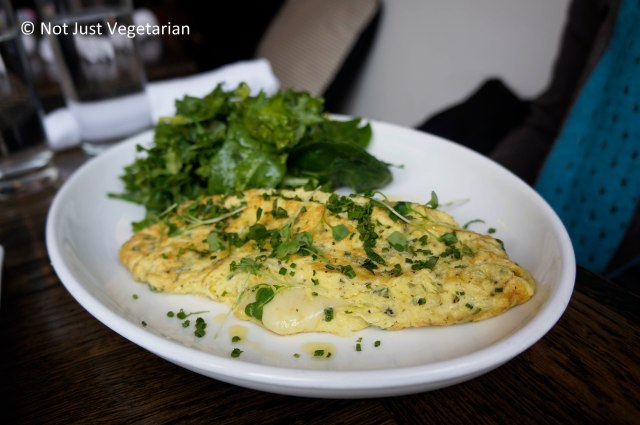 Two egg omlette with gruyere and fine herbs served and a side of herbs at Tremont NYC