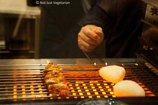 Chicken negi and rice cake being grilled at Yopparai NYC