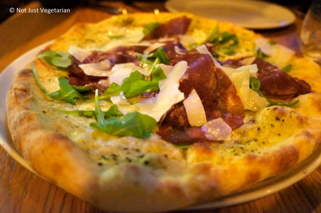Wood fired thin crust pizza topped with pesto,  bresaola, rocket, parmesan, and truffle oil at Goat in Chelsea, London