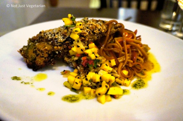 Aubergine Teriyaki (Char-grilled aubergine layered with coriander pesto, roasted red peppers, shitake mushrooms and horseradish, coated with crispy breadcrumbs and served on stir-fried noodles with a pickled ginger and mango salsa) at The Gate Islington in London