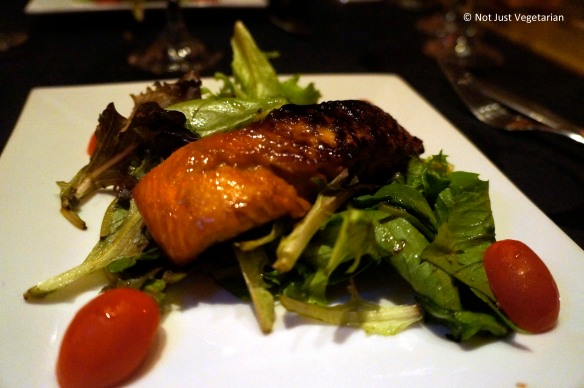 Asian marinated grilled salmon on a bed of mixed greeens at Masq restaurant and lounge, NYC