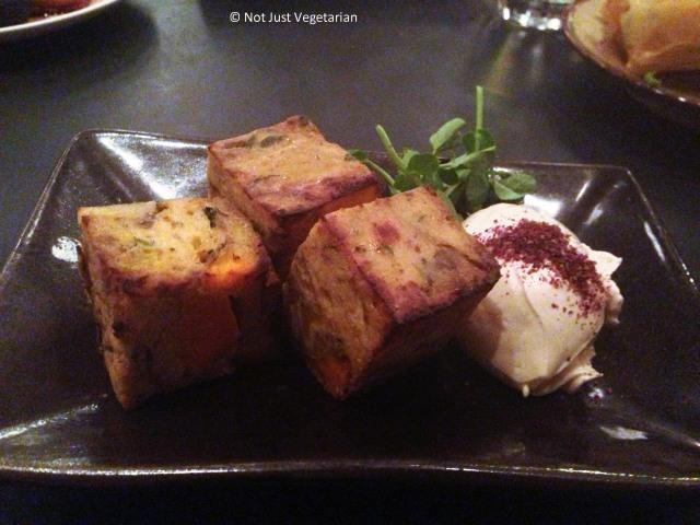 Plantain, feta and sweet potato tortilla with pomegranate labneh and pea shoots at Kopapa in London